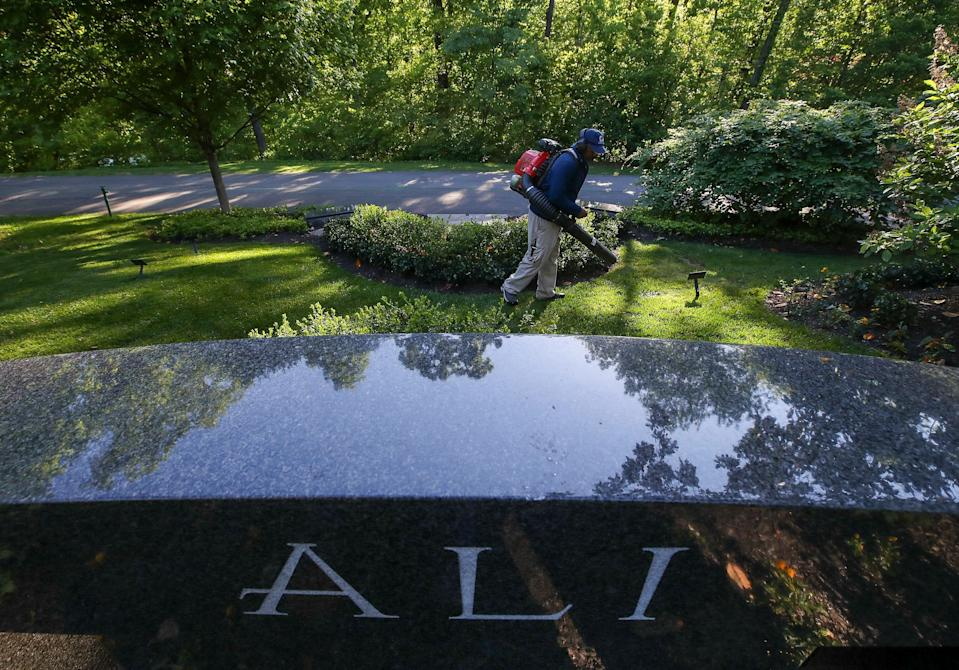 Danny Key uses a blower to clear off debris from Muhammad Ali's gravesite at Cave Hill Cemetery.