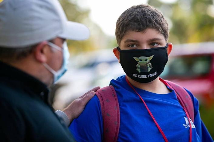 James Orlowsky, left, drops off his son, Noah Orlowsky, a seventh-grader at Miami Beach Nautilus Middle School, for in-person classes on Friday, Oct. 9, 2020.