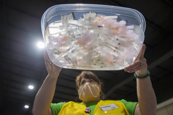 Staff of Ochsner Health carry trays filled with syringes containing the Johnson & Johnson COVID-19 vaccine as people come into the Castine Center in Pelican Park to be vaccinated in Mandeville, La., on Wednesday, March 10, 2021. (Chris Granger /The Advocate via AP)