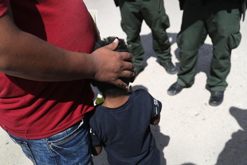 U.S. Border Patrol agents take a father and son from Honduras into custody near the U.S.-Mexico border on June 12 near Mission, Texas.