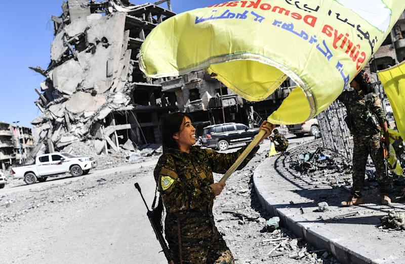 Rojda Felat, the female commander of the Syrian Democratic Forces' battle for Raqa, waves the alliance's flag in Al-Naim square after proclaiming victory on October 17, 2017 (AFP Photo/BULENT KILIC)
