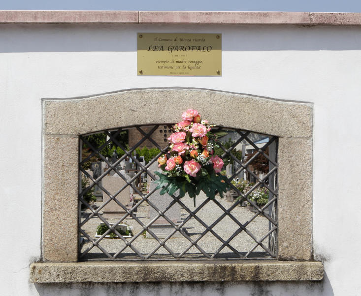 In this photo taken Friday, Aug. 3, 2012, the municipality of Monza commemorates Lea Garofalo with flowers and a plaque as an example of courage as a witness for legality, at a cemetery wall near the spot where she was murdered in Monza, near Milan, Italy. Grofalo, a woman who dared to cooperate with police in the fight against a dreaded Italian mob network was murdered, her body dumped in a barrel of acid in the countryside near Milan. Her 17-year-old daughter stepped forward and testified, helping to send six people to prison for life. (AP Photo/Antonio Calanni)