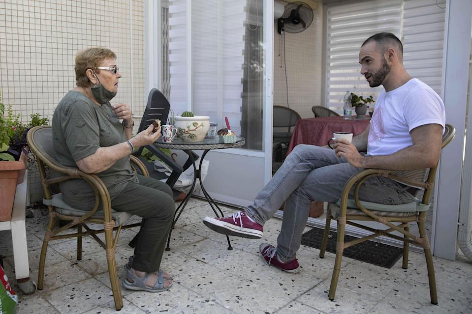 Israeli Itamar Glazer, right, sits with 85-year-old Holocaust survivor Sara Weinsten during a visit in Yavne, Israel, Thursday, Oct. 8, 2020. For thousands of older Israelis like Weinsten, being housebound alone during Israel's second nationwide lockdown due to the coronavirus pandemic is difficult and depressing. But each week ahead of the Jewish Sabbath, which starts on Friday at sundown, a home-baked cake is delivered by one of thousands of volunteers bringing pastries to home-bound older Israelis. (AP Photo/Sebastian Scheiner)