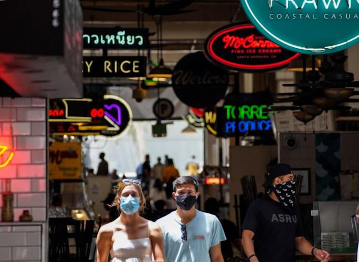 "People wearing masks in downtown Los Angeles at Grand Central Market. The responsibility for enforcing mask requirements largely falls on employees. <span class=""copyright"">(Kent Nishimura / Los Angeles Times)</span>"