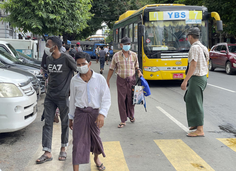 Commuters wearing face masks walk on a street after getting off a bus in Yangon, Myanmar, Thursday, July 8, 2021. Myanmar is facing a a rapid rise in COVID-19 patients and a shortage of oxygen supplies just as the country is consumed by a bitter and violent political struggle since the military seized power in February. (AP Photo)