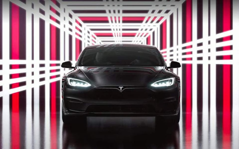 A sleep black Tesla car sits face on to the camera, framed by a corridor of bright white and red neon in a plaid pattern - Telegraph/Tesla