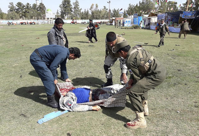 A wounded man is tended to following multiple explosions in Lashkar Gah city of Helmand province, southern Afghanistan, Saturday, Mar. 23, 2019. An Afghan official says that at least three have been killed in twin bomb explosions occurred during the Farmer's Day ceremony in southern Helmand province. (AP Photo/Abdul Khaliq)