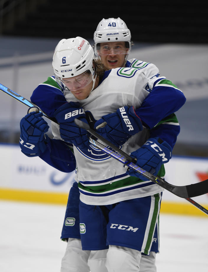 Vancouver Canucks' Brock Boeser (6) and Elias Pettersson (40) celebrate a goal against the Edmonton Oilers during the third period of an NHL hockey game Wednesday, Jan. 13, 2021, in Edmonton, Alberta. (Dale MacMillan/The Canadian Press via AP)
