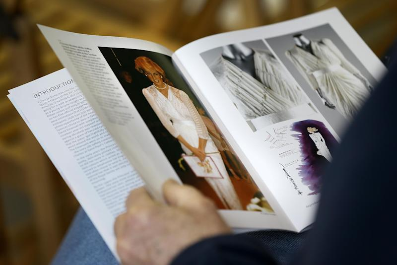 An auction attendee reads the catalogue ahead of the Kerry Taylor 'Fit for a Princess' auction in London, Tuesday, March 19, 2013. The auction was of ten dresses formerly owned and worn by Britain's Princess Diana. The total hammer price for the ten lots was 719,000 pounds ($1.09 million US) not including the 20 percent buyers premium . (AP Photo/Kirsty Wigglesworth)