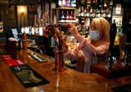 A woman wearing a face mask works behind a bar at the Grapes pub in Liverpool