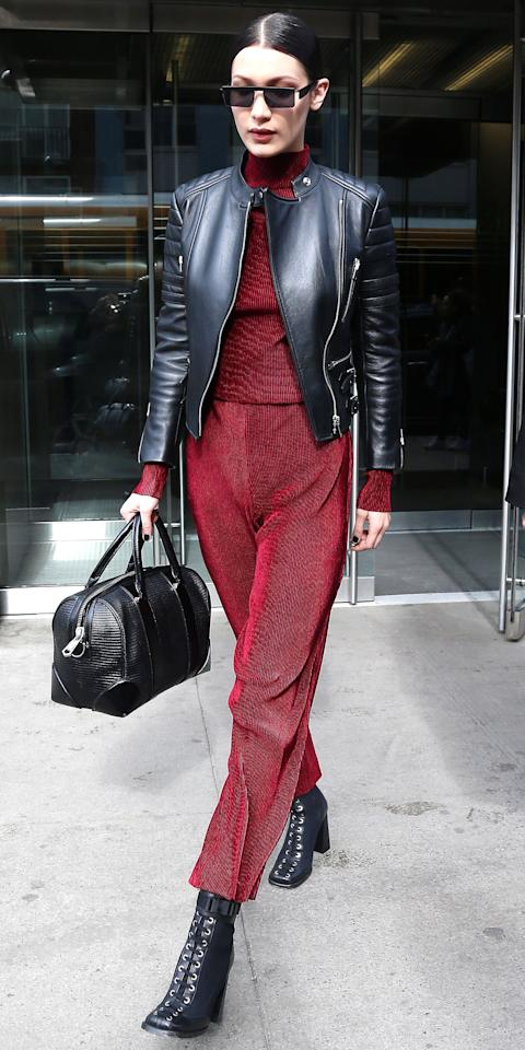"<p>We are seriously loving Hadid's red separates, wide-leg pants and a turtleneck sweater, effortlessly paired with a leather jacket, lace-up booties (get a similar pair <a rel=""nofollow"" href=""https://click.linksynergy.com/fs-bin/click?id=93xLBvPhAeE&subid=0&offerid=390098.1&type=10&tmpid=8157&RD_PARM1=http%253A%252F%252Fshop.nordstrom.com%252Fs%252Fjeffrey-campbell-legion-high-heel-boot-women%252F4397339%253Forigin%253Dcategory-personalizedsort%2526fashioncolor%253DBLACK%252520BOX%252520LEATHER&u1=ISBellaHadid3.21JA"">here</a>), and a structured black bag. </p>"