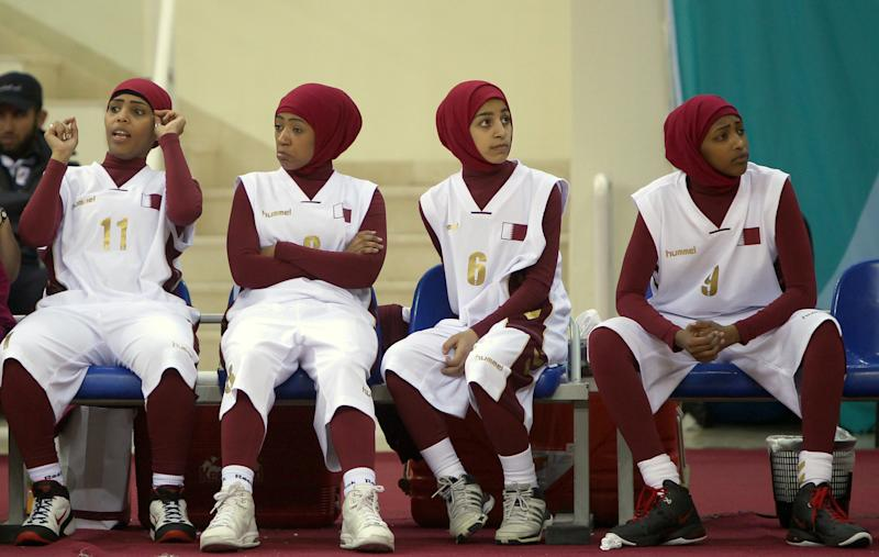 Qatari players wearing Islamic sportswear especially designed for women sit on the bench during their 2011 Arab Games basketball match against Lebanon in Doha on December 19, 2011 (AFP Photo/Marwan Naamani)