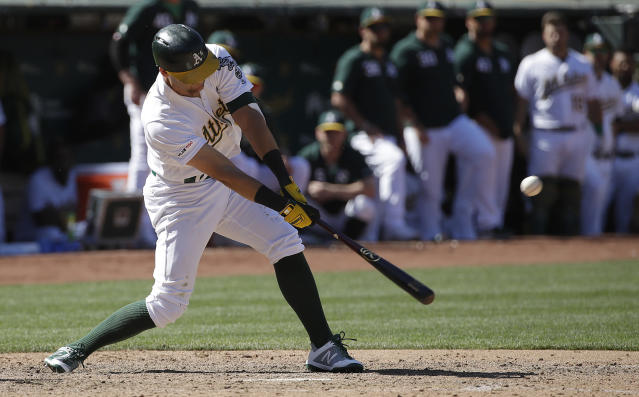 Oakland Athletics' Chad Pinder hits an RBI-single against the Texas Rangers during the ninth inning of a baseball game in Oakland, Calif., Wednesday, April 24, 2019. (AP Photo/Jeff Chiu)