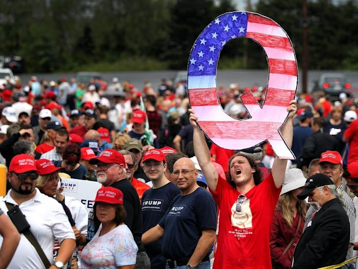 Trump supporter holds up a QAnon sign at rally.