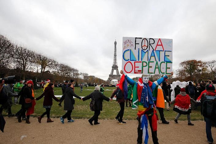 """A demonstrator wearing a mask of the Anonymous group holds a banner reading """"For a climate of Peace"""" at a rally on the Champs de Mars near the Eiffel Tower in Paris on December 12, 2015 on the sidelines of COP21, the UN conference on global warming (AFP Photo/FRANCOIS GUILLOT)"""