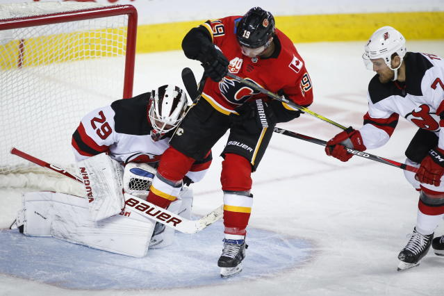 New Jersey Devils goalie Mackenzie Blackwood, left, traps the skate of Calgary Flames' Matthew Tkachuk , center, while stopping a shot, as Matt Tennyson watches during the third period of an NHL hockey game Thursday, Nov. 7, 2019, in Calgary, Alberta. (Jeff McIntosh/The Canadian Press via AP)