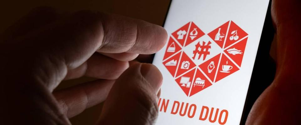 PinDuoDuo company logo on the smartphone hold in hands.