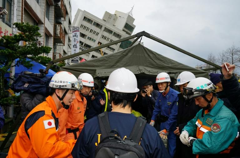 Japanese rescue personnel in front of a collapsed building in Hualien on February 8, 2018