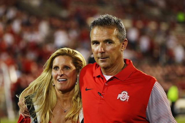 Head coach Urban Meyer of the Ohio State Buckeyes walks off the field alongside his wife Shelley after his team won 45-24 against the Oklahoma Sooners at Gaylord Family Oklahoma Memorial Stadium on September 17, 2016 in Norman, Oklahoma. (Getty)
