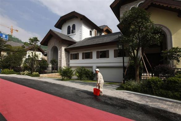 A cleaner stands in front of a house for sale at the replica village of Austria's UNESCO heritage site, Hallstatt, in China's southern city of Huizhou in Guangdong province, June 1, 2012.