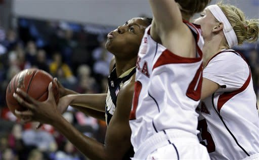 Purdue forward Drey Mingo, left, drives to the basket against Nebraska guard Lindsey Moore, center, forward Emily Cady during the first half of an NCAA college basketball game in the Big Ten Conference tournament in Hoffman Estates, Ill., on Saturday, March 9, 2013. (AP Photo/Nam Y. Huh)