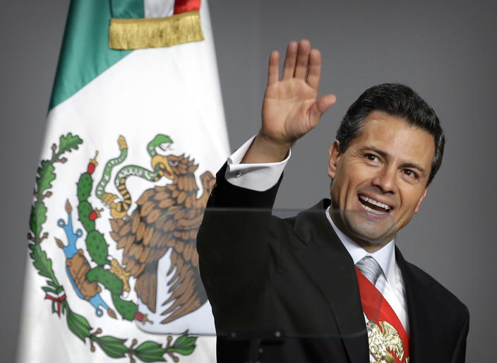 Mexico's newly sworn-in President Enrique Pena Nieto waves to the audience after delivering his inaugural speech at the National Palace in Mexico City, Saturday, Dec. 1, 2012. Protesters opposed to the new president clashed with tear gas-wielding police early Saturday morning outside the National Congress, where Pena Nieto took the oath of office. (AP Photo/Andres Leighton)