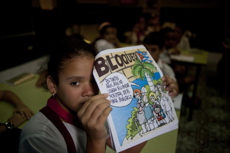 Daniela de la Caridad poses for a photo with her homework about the embargo against Cuba at the Angela Landa elementary school in Old Havana, Cuba, Tuesday, Nov. 13, 2012. The U.N. General Assembly on Tuesday voted overwhelmingly to condemn the U.S. commercial, economic and financial embargo against Cuba for the 21st year in a row. The embargo was first enacted in 1960 following Cuba's nationalization of properties belonging to U.S. citizens and corporations. (AP Photo/Ramon Espinosa)