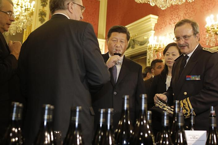Chinese President Xi Jinping, center, tastes wine during a display by local producers before a dinner at the town hall in Lyon, central France, Tuesday, March 25, 2014. Xi Jinping arrived in France for a three-day state visit. (AP Photo/Laurent Cipriani, Pool)