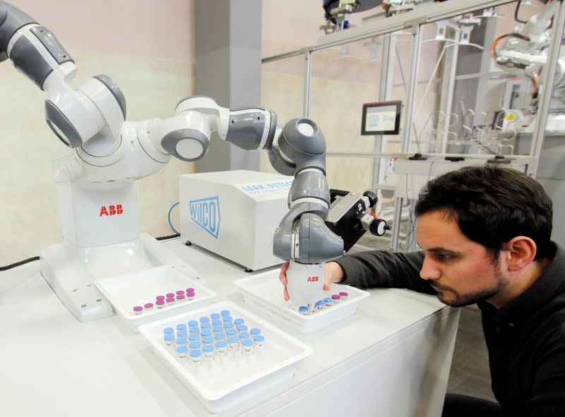 FILE PHOTO: Engineer Trilla of ABB adjusts an arm of a YuMi - IRB14000 robot in Baden