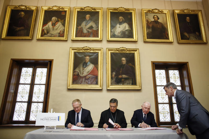 Francois-Henri Pinault, CEO of French luxury group Kering, left, his father Francois Pinault, right, and Archbishop of Paris Michel Aupetit, center, sign an agreement to raise money for the rebuild of Notre-Dame cathedral, in Paris, Tuesday, Oct. 1, 2019. French billionaire Francois Pinault and his son Francois-Henri Pinault have made a 100 million euros ($109 million) donation for the rebuilding of Notre Dame Cathedral. (AP Photo/Thibault Camus)