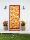 """<p>Done properly, a simple candy corn front door design will be the talk of your entire block. You can have the kids pitch in to craft this one!</p><p><strong>Craft the Door: </strong>Create a candy corn-inspired """"quilt."""" Paint wide stripes, using acrylic paint (we used orange, mustard, cranberry, and gray), on thick artist's paper. Once dry, cut into equal-size triangles. Cut a 2-inch paper trim in a corresponding color. Attach to door using double- sided tape. </p>"""