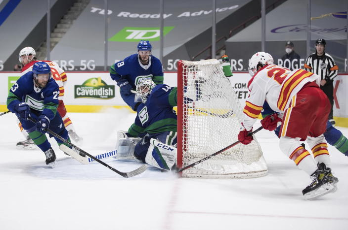 Vancouver Canucks goalie Braden Holtby (49) stops Calgary Flames' Dillon Dube, right, during the third period of an NHL hockey game, Sunday, May 16, 2021, in Vancouver, British Columbia. (Darryl Dyck/The Canadian Press via AP)