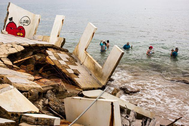 People swim by the ruins of a structure damaged during Hurricane María. (Photo: Erika P. Rodriguez for HuffPost)