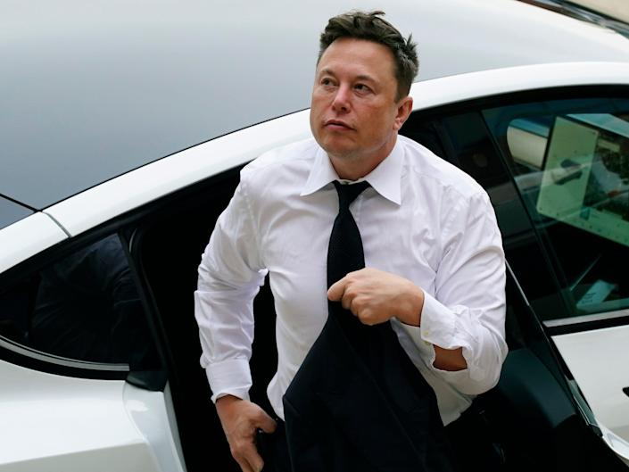 Tesla CEO Elon Musk in a white shirt and tie exits the backseat of a white Tesla