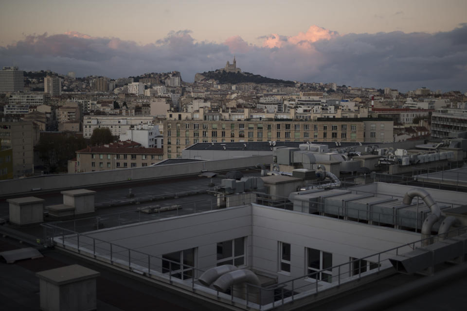 Marseille's Notre-Dame de la Garde basilica is pictured from the roof of the La Timone hospital at sunrise. Friday, Nov. 13, 2020. France is more than two weeks into its second coronavirus lockdown, and intensive care wards have been over 95% capacity for more than 10 days now. Marseille has been submerged with coronavirus cases since September. (AP Photo/Daniel Cole)