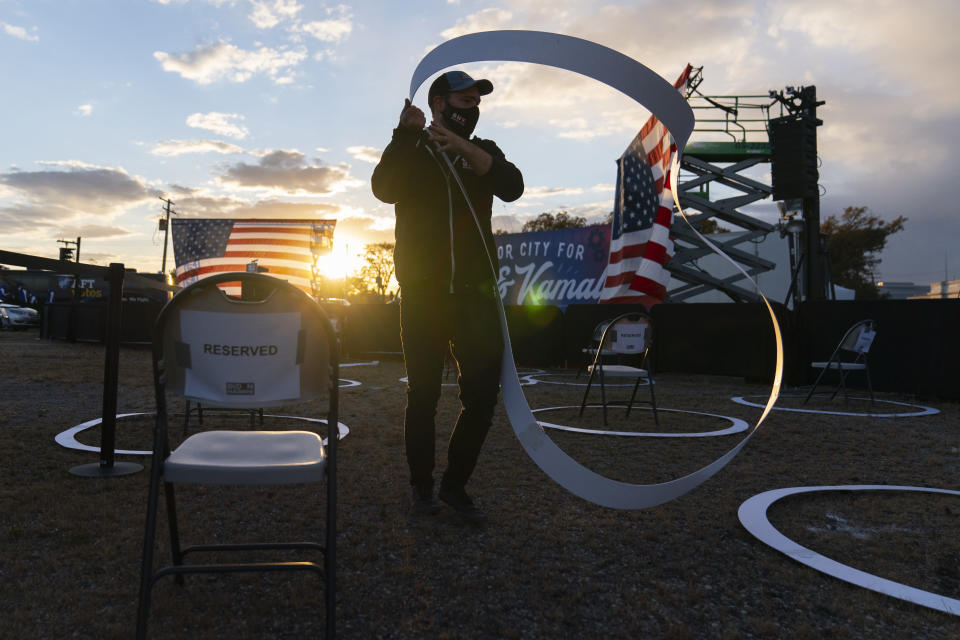 FILE - In this Oct. 16, 2020, file photo a worker places social distancing circles around chairs before Democratic presidential candidate former Vice President Joe Biden arrives to speak at Michigan State Fairgrounds in Novi, Mich.. (AP Photo/Carolyn Kaster, File)