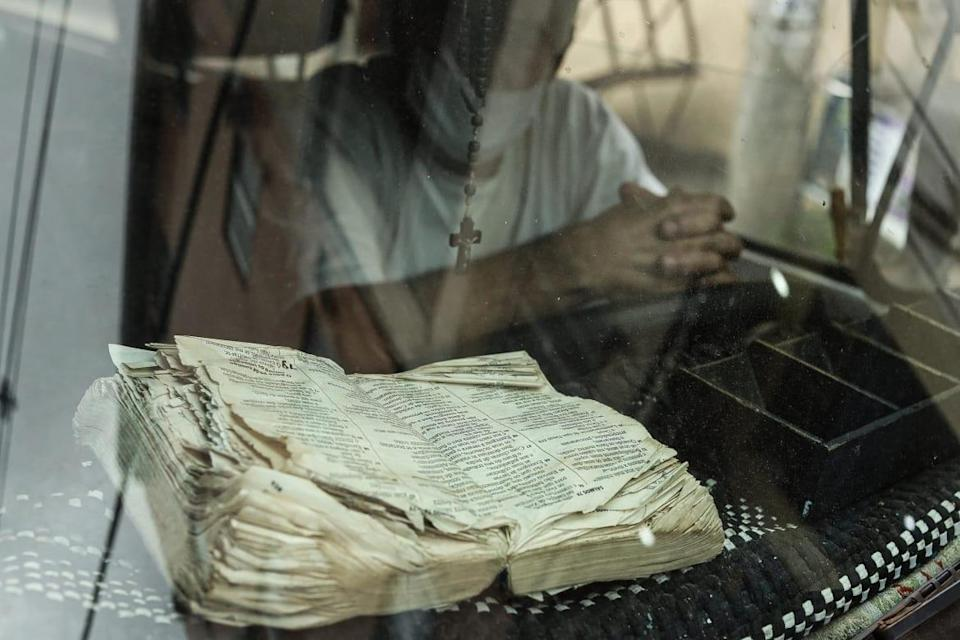"""<div class=""""inline-image__caption""""><p>A priest is waiting in a car, , his Bible inside the hot favela of Trabajaras. These priests go around the favelas blessing people, especially gang members.</p></div> <div class=""""inline-image__credit"""">Courtesy Jonathan Alpeyrie</div>"""
