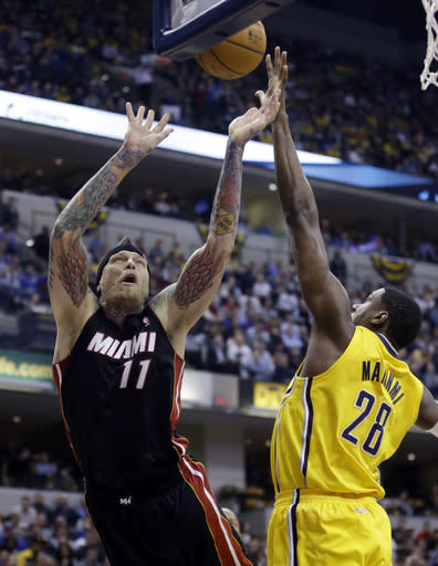 Indiana Pacers center Ian Mahinmi, right, blocks the shot of Miami Heat forward Chris Andersen in the first half of an NBA basketball game in Indianapolis, Tuesday, Dec. 10, 2013. (AP Photo/Michael Conroy)