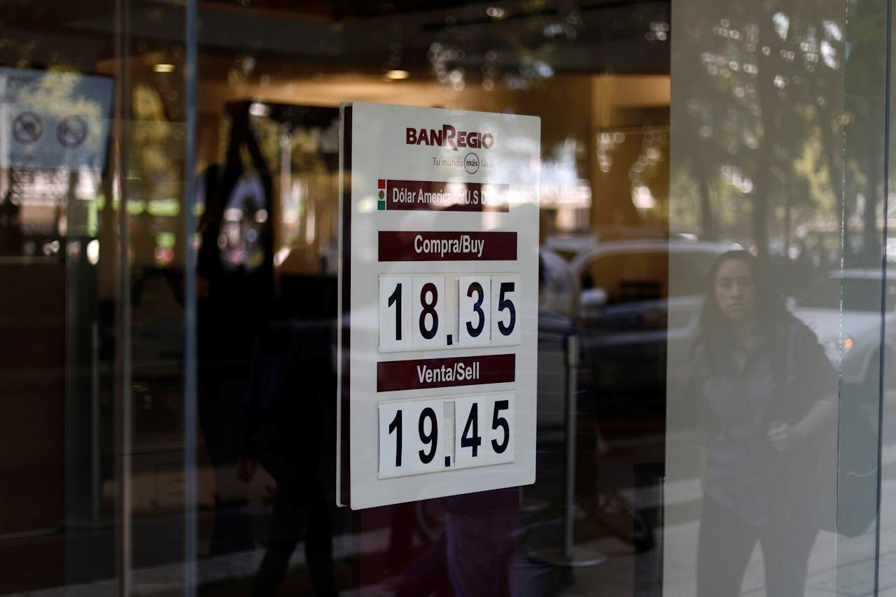 A woman is reflected in a window as she walks past a board displaying the exchange rate for the Mexican peso against the U.S. dollar at a foreign exchange house in Mexico City, Mexico, October 20, 2017. REUTERS/Edgard Garrido