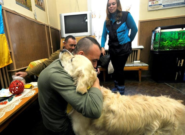 "Former Minister for Veterans' Affairs Oksana Kolyada looks on as a soldier who was admitted for treatment, plays with ""therapy dog"" Ricky, who helps him overcome his post-conflict trauma"