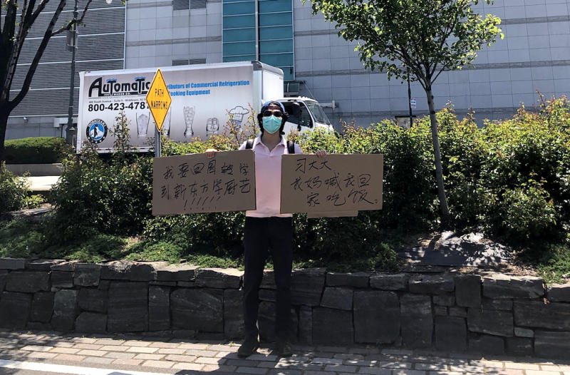 Recent New York University graduate Jiang Li says he has been trying to purchase tickets back to China since April but has been unable to return. Late last month, he showed up to the Chinese Consulate in New York with a sign saying that his mom is waiting on him for dinner back home. (Courtesy Jiang Li)