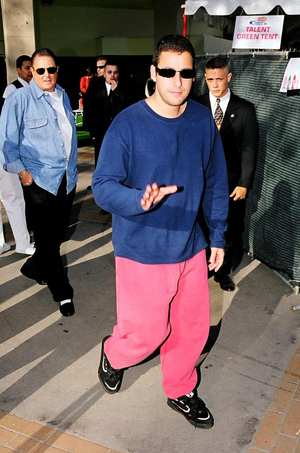 <p>While most celebs get gussied up for awards shows, Adam Sandler keeps it casual. He hit the 1999 Kids' Choice Awards in this comfy pink-and-blue sweatsuit combo. (Photo: Jeff Kravitz/FilmMagic)</p>