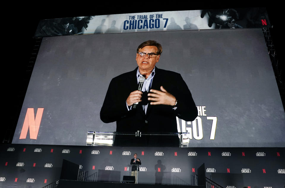 """FILE - Aaron Sorkin, writer/director of """"The Trial of the Chicago 7,"""" appears on the movie screen as he introduces the film at its drive-in premiere in Pasadena, Calif. on Oct. 13, 2020. (AP Photo/Chris Pizzello, File)"""