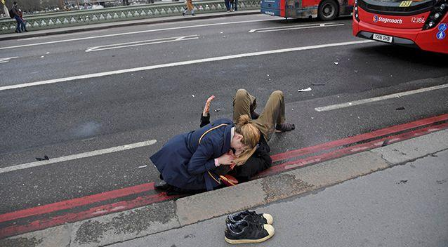A woman assists a person injured in the attack in London on Wednesday. Photo: Reuters