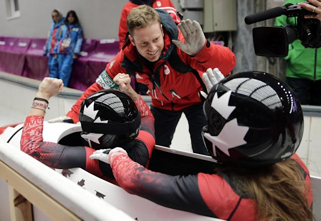 The team from Canada CAN-1, piloted Kaillie Humphries with brakeman Heather Moyse, cross into the finish area to win the gold medal in the women's bobsled competition at the 2014 Winter Olympics, Wednesday, Feb. 19, 2014, in Krasnaya Polyana, Russia. (AP Photo/Jae C. Hong)