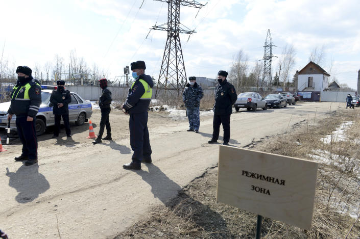"Police officers wearing face masks to protect against coronavirus guard an entrance of the prison colony IK-2, which stands out among Russian penitentiary facilities for its particularly strict regime, with the sign reads ""Security zone"", in Pokrov in the Vladimir region, 85 kilometers (53 miles) east of Moscow, Russia, Tuesday, April 6, 2021. Doctors from the Navalny-backed Alliance of Doctors announced going to the Pokrov prison on Tuesday to demand the opposition leader gets qualified medical help from independent doctors after he complained about pain in his leg and back. (AP Photo/Denis Kaminev)"