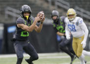 Oregon's Travis Dye, left, pulls down a pass reception ahead of UCLA's Datona Jackson, right, during the first quarter of an NCAA college football game Saturday, Nov. 21, 2020, in Eugene, Ore. (AP Photo/Chris Pietsch)