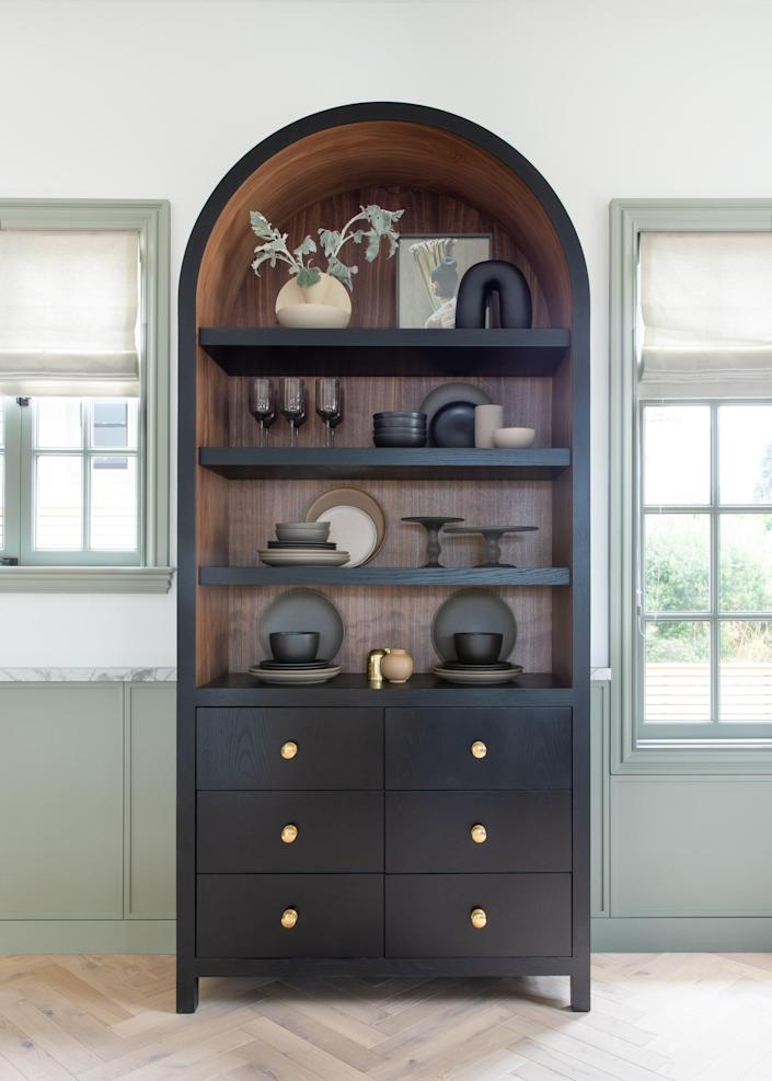 """<div class=""""caption""""> The walnut cabinet fits between two windows of varying heights. Not only does it trick the eye to make the area appear symmetrical, but because the kitchen has no upper cabinetry, it was important to have a functional piece. </div>"""