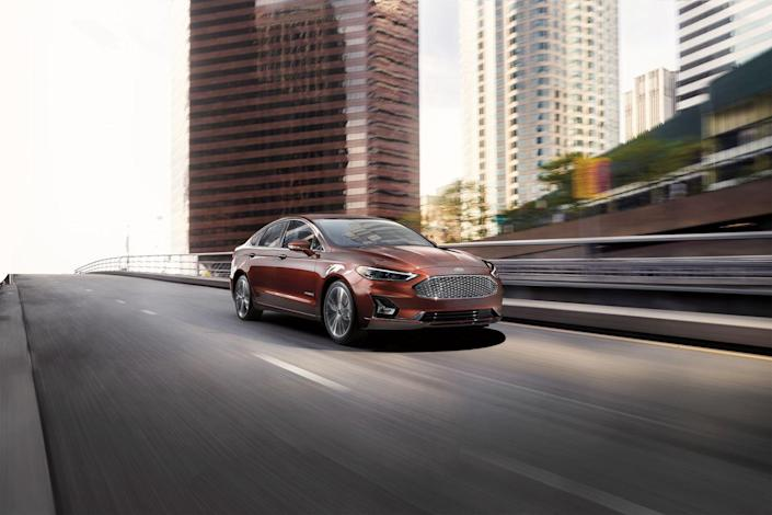 """<p>A mild refresh gives the <a href=""""https://www.caranddriver.com/ford/fusion"""" rel=""""nofollow noopener"""" target=""""_blank"""" data-ylk=""""slk:2019 Ford Fusion Hybrid"""" class=""""link rapid-noclick-resp"""">2019 Ford Fusion Hybrid</a> a new look, while <a href=""""https://www.caranddriver.com/news/a19496442/ford-refreshes-the-fusion-again-and-debuts-co-pilot360-safety-package/"""" rel=""""nofollow noopener"""" target=""""_blank"""" data-ylk=""""slk:its adoption of the new Ford Co-Pilot360"""" class=""""link rapid-noclick-resp"""">its adoption of the new Ford Co-Pilot360</a> active safety suite adds some notable standard safety features, such as automated emergency braking, lane-keep assist, and blind-spot monitoring. In terms of efficiency, however, the Fusion hybrid's 42-mpg combined rating lags behind some of its newer competitors.<br></p>"""