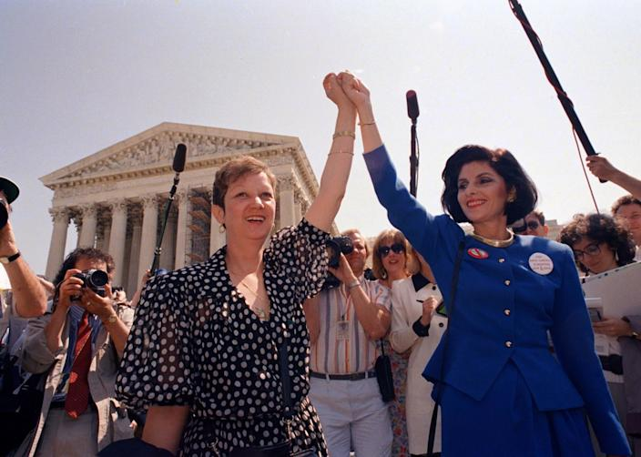"""Norma McCorvey, left, and her attorney Gloria Allred hold hands as they leave the Supreme Court building in Washington after sitting in while the court listened to arguments in a Missouri abortion case in 1989. <span class=""""copyright"""">(J. Scott Applewhite / AP)</span>"""